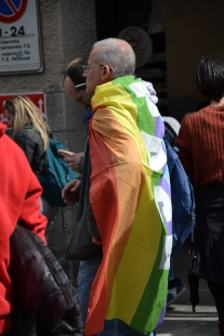 A man with a peace flag on his shoulder